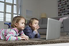 Brother and sister using laptop on carpet in living room - stock photo
