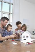 Family of four constructing house model Stock Photos