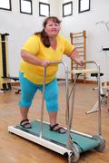 overweight woman running on trainer treadmill - stock photo