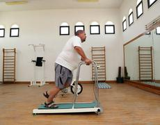Overweight man running on trainer treadmill Stock Photos