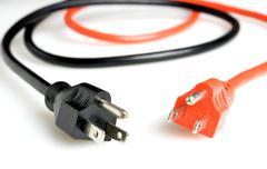 Orange and a black power plugs Stock Photos