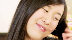 Dolly shot of happy asian american woman brushing long hair in bed Stock Footage