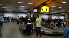 Passengers wait for luggages on the babbage belt at Guarulhos Airport - stock footage