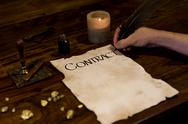 Stock Photo of medieval looking man writes a contract