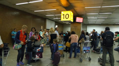 Passengers wait for luggages on the babbage belt at Guarulhos Airport Stock Footage
