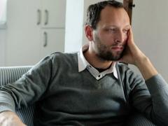 Sad, unhappy young handsome man sitting in armchair at home NTSC Stock Footage