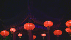 Chinese lanterns swaying in front of pagoda Stock Footage