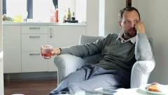 Sad, unhappy young handsome man sitting in armchair at home HD Stock Footage