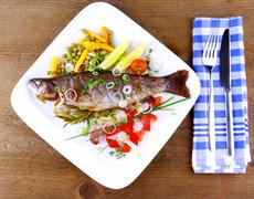 grilled trout and quite fine vegetables with cutlery - stock photo