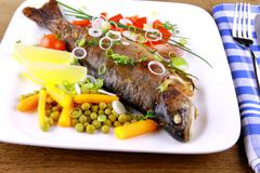 grilled trout with quite fine vegetables, cutlery - stock photo