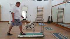 fitness - overweight man running on trainer treadmill - stock footage