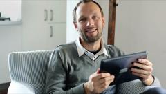 Portrait of young happy man with tablet computer at home HD Stock Footage