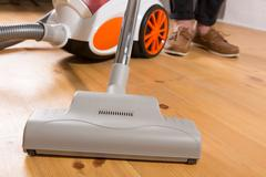 cleaning with vacuum cleaner in living room - stock photo