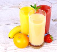 bananas, strawberry and oranges juice in glass - stock photo