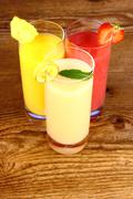 banana, strawberry and pineapple juice in glass - stock photo