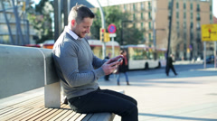 Happy man playing on smartphone and sitting on street bench. Stock Footage