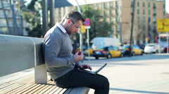 Man finishing work on a laptop and eating croissant on street bench. Stock Footage
