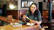 Stock Video Footage of Businesswoman eating croissant using cellphone in cafe, steadycam shot.