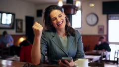 Businesswoman getting good news using cellphone in cafe, steadycam shot. Stock Footage