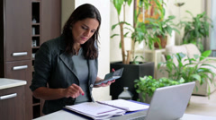 Happy businesswoman talking on cellphone in office, steadycam shot. Stock Footage