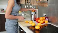 Businesswoman preparing orange juice in kitchen, steadycam shot. Stock Footage