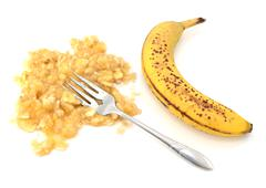 spotty ripe banana with mashed flesh and fork - stock photo