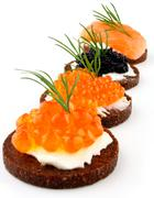 pumpernickel bread with salmon, trout and sturgeon caviar - stock photo