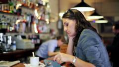 Businesswoman waiting in cafe and looking on cellphone, steadycam shot. Stock Footage