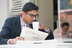 Young indian business man on laptop and coffee at a cafe Stock Photos