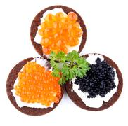 pumpernickel bread topped with red and black caviar - stock photo