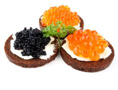 pumpernickel bread with red and black caviar - stock photo