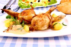 two fried quail with gravy, gnocchi, rosemary and caviar salad - stock photo