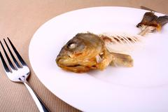 complete bone of whole fish on plate, abstract - stock photo