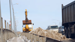 Snow removal equipment (excavator) cleans the road from snow Stock Footage
