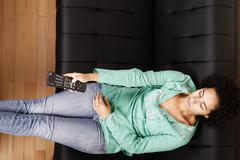brazilian woman with remote control. - stock photo