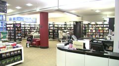 Time lapse of staff serving customers in a busy UK book store Stock Footage