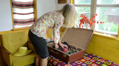 Blond woman girl unpack her clothes into retro travel suitcase Stock Footage