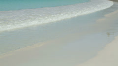 Turquoise water, waves gently roll onto a white sandy beach Stock Footage