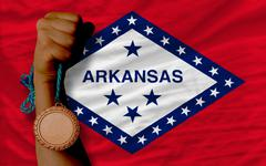 bronze medal for sport and  flag of american state of arkansas - stock photo