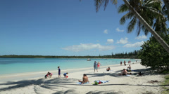 Tourists sunbathe on tropical beach, isle of pines, new caledonia Stock Footage