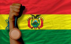 Stock Photo of bronze medal for sport and  national flag of bolivia