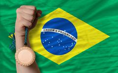 bronze medal for sport and  national flag of brazil - stock photo