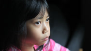 Stock Video Footage of Thoughtful Little Asian Girl Looks At The Camera