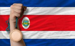 Stock Photo of bronze medal for sport and  national flag of costarica