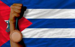 bronze medal for sport and  national flag of cuba - stock photo