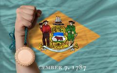 bronze medal for sport and  flag of american state of delaware - stock photo
