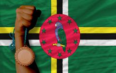 bronze medal for sport and  national flag of dominica - stock photo