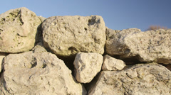 Dolly: Stone wall of ancient ruins at archaeological site - stock footage