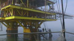 Ship moored to offshore gas production platform - stock footage