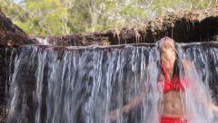Woman in bikini under waterfall Stock Footage